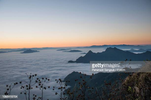 scenic view of snowcapped mountains against sky at sunset - pattanasit stock pictures, royalty-free photos & images