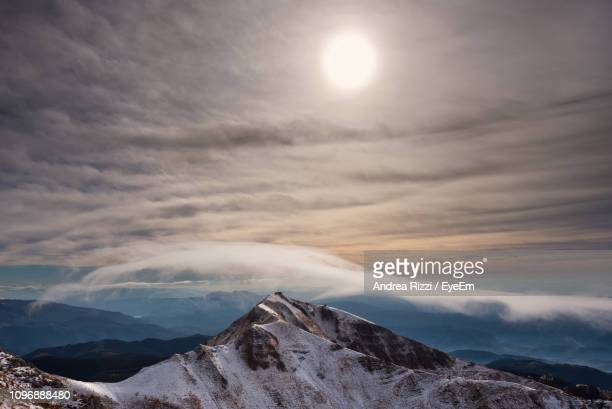scenic view of snowcapped mountains against sky during sunset - andrea rizzi stockfoto's en -beelden