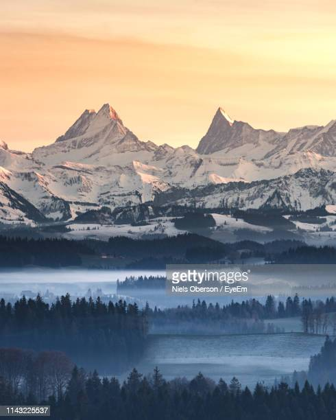 scenic view of snowcapped mountains against sky during sunset - bern canton stock pictures, royalty-free photos & images