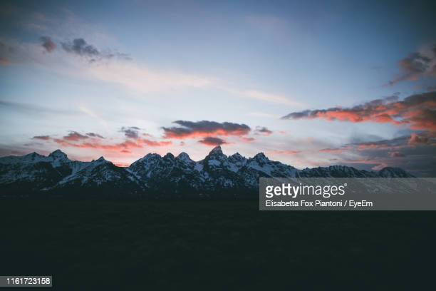 scenic view of snowcapped mountains against sky during sunset - ティトン山脈 ストックフォトと画像