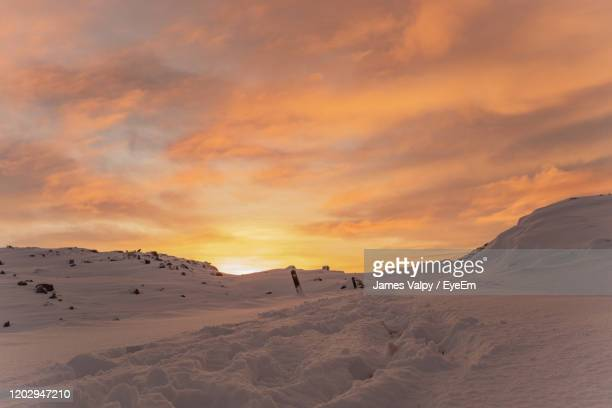 scenic view of snowcapped mountains against sky during sunset - snow stock pictures, royalty-free photos & images