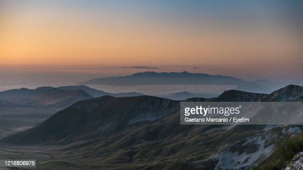 scenic view of snowcapped mountains against sky during sunset - parco nazionale d'abruzzo foto e immagini stock