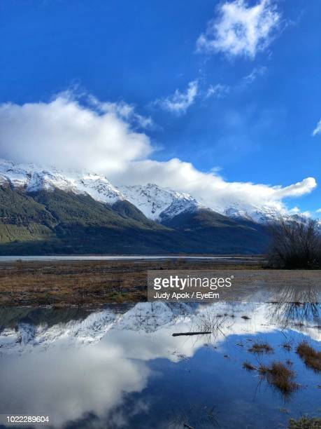 scenic view of snowcapped mountains against sky - judy winter stock-fotos und bilder