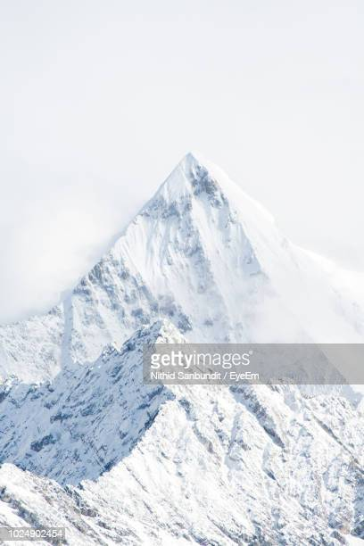 scenic view of snowcapped mountains against sky - bergpiek stockfoto's en -beelden