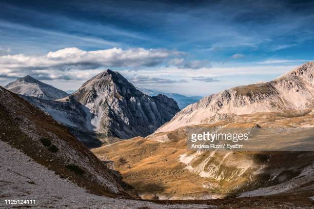 scenic view of snowcapped mountains against sky - andrea rizzi stockfoto's en -beelden