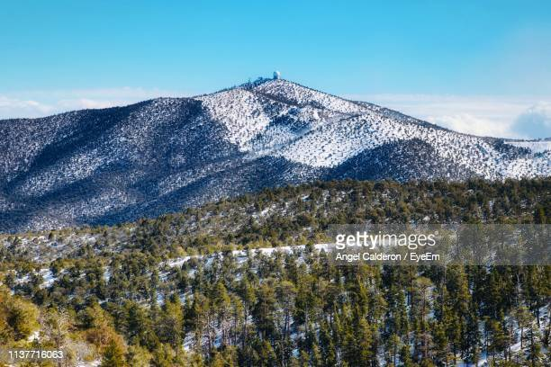 scenic view of snowcapped mountains against sky - mt charleston stock photos and pictures
