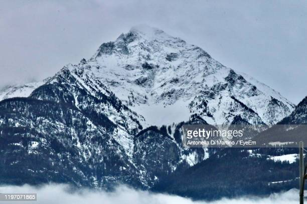scenic view of snowcapped mountains against sky - antonella di martino foto e immagini stock
