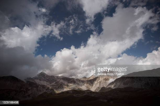 scenic view of snowcapped mountains against sky - andrea rizzi stock-fotos und bilder