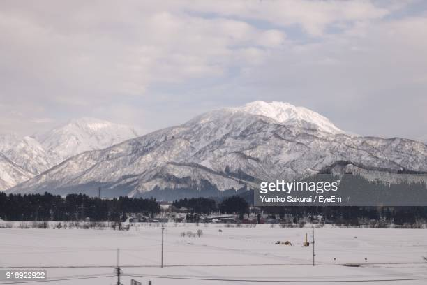 scenic view of snowcapped mountains against sky - 新潟県 ストックフォトと画像