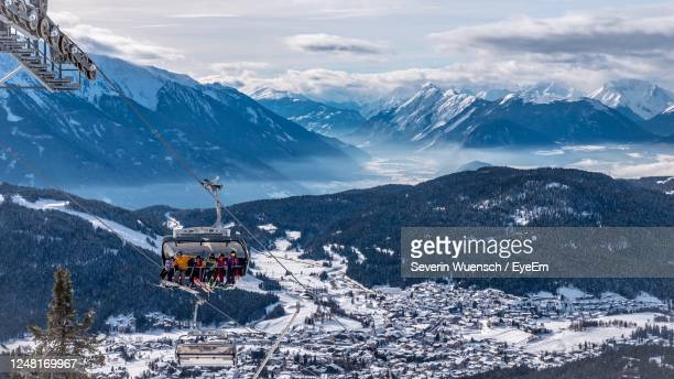scenic view of snowcapped mountains against sky with cable car - ゼーフェルト ストックフォトと画像