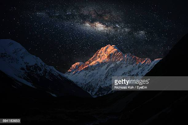 scenic view of snowcapped mountains against star field - chaîne de montagnes photos et images de collection