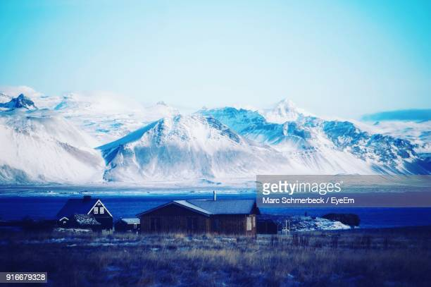 Scenic View Of Snowcapped Mountains And Sea Against Blue Sky