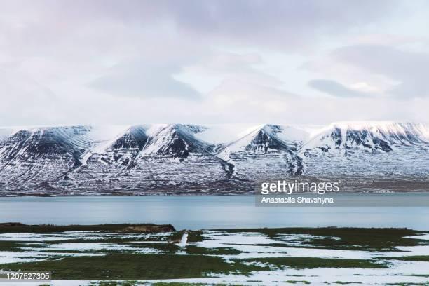 schilderachtig uitzicht op besneeuwde bergen en zee aan de fjord van ijsland - seascape stockfoto's en -beelden