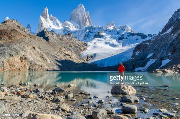 scenic view of snowcapped mountains by lake against sky - argentina stock pictures, royalty-free photos & images