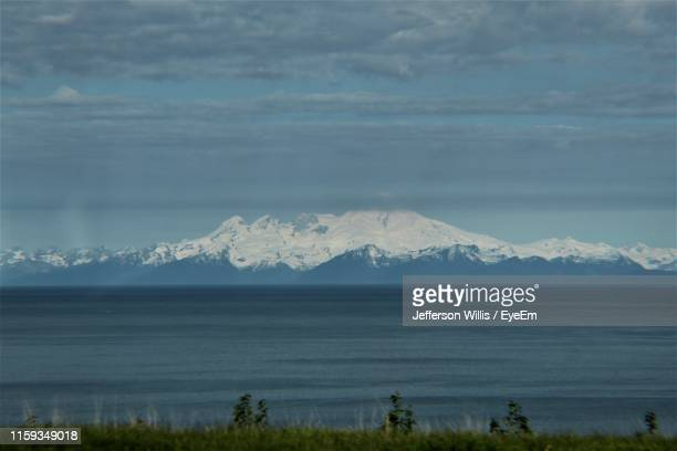 scenic view of snowcapped mountains by sea against sky - home run ストックフォトと画像