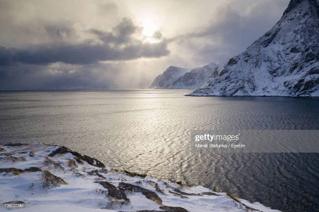 Scenic View Of Snowcapped Mountains By Sea Against Sky : Stock Photo