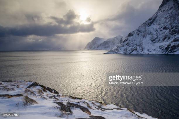 scenic view of snowcapped mountains by sea against sky - marek stefunko stockfoto's en -beelden