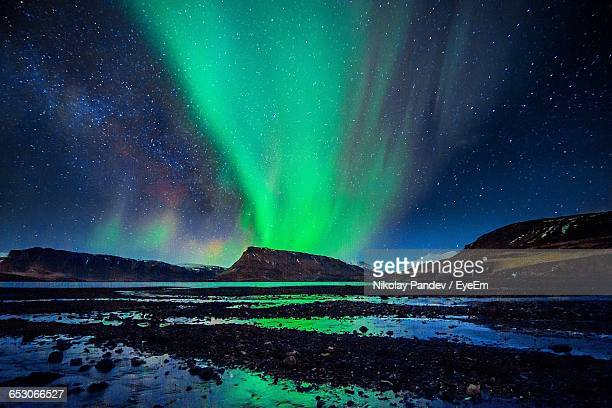 scenic view of star constellation and aurora over landscape - aurora australis stock pictures, royalty-free photos & images