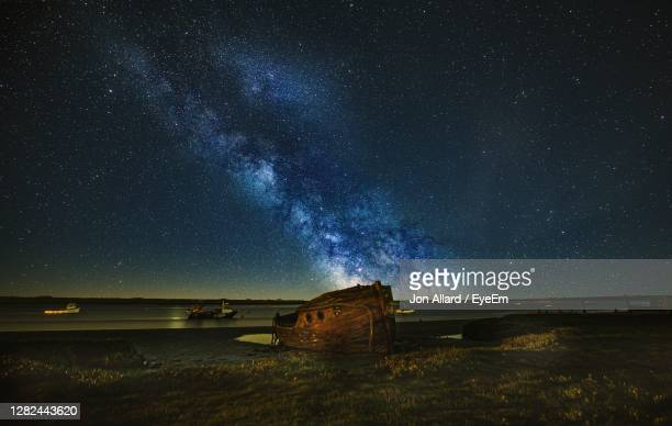 scenic view of star field against sky at night over shipwreck - astronomy stock pictures, royalty-free photos & images