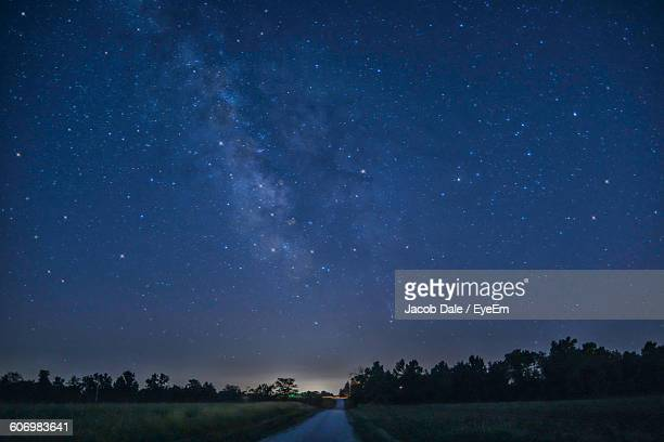 Scenic View Of Starry Sky Over Road Amidst Field