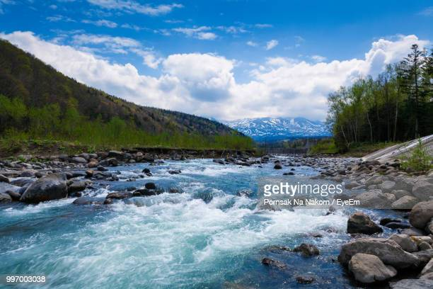 scenic view of stream against sky - flowing stock pictures, royalty-free photos & images