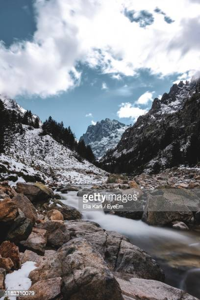 scenic view of stream amidst rocks against sky during winter - elia karli stock-fotos und bilder