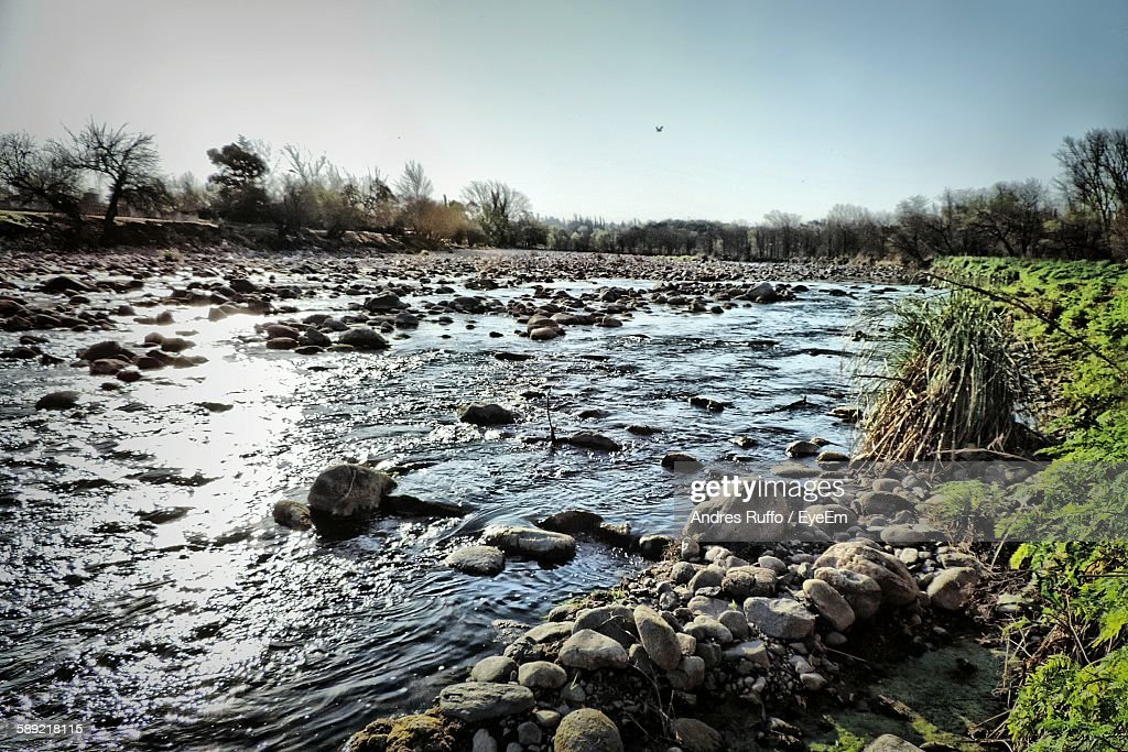 Scenic View Of Stream Through Rocks Against Sky : Stock Photo