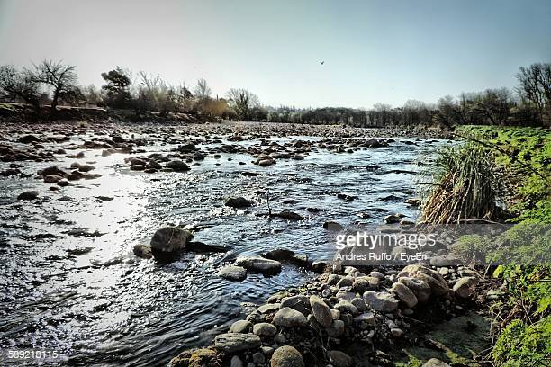 scenic view of stream through rocks against sky - andres ruffo stock-fotos und bilder