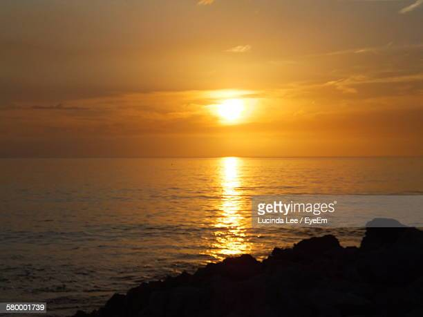 scenic view of sun reflecting on sea during sunset - lucinda lee stock photos and pictures