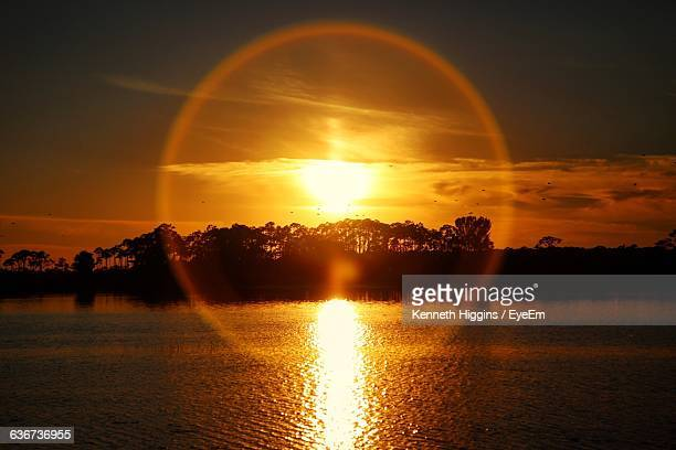 Scenic View Of Sun Shining Over Lake And Silhouette Trees During Sunset