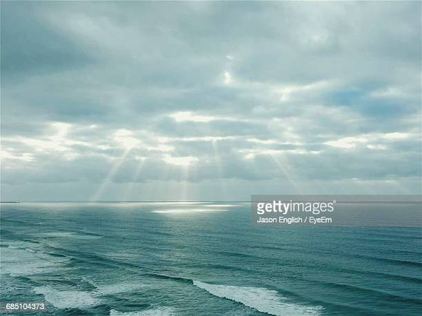 Scenic View Of Sunbeams Streaming From Clouds Over Sea
