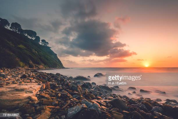 scenic view of sunset at rocky shore by sea against sky - rancho palos verdes stock pictures, royalty-free photos & images