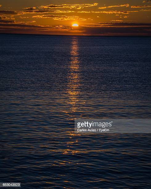 scenic view of sunset over calm sea - carlos aviles stock pictures, royalty-free photos & images