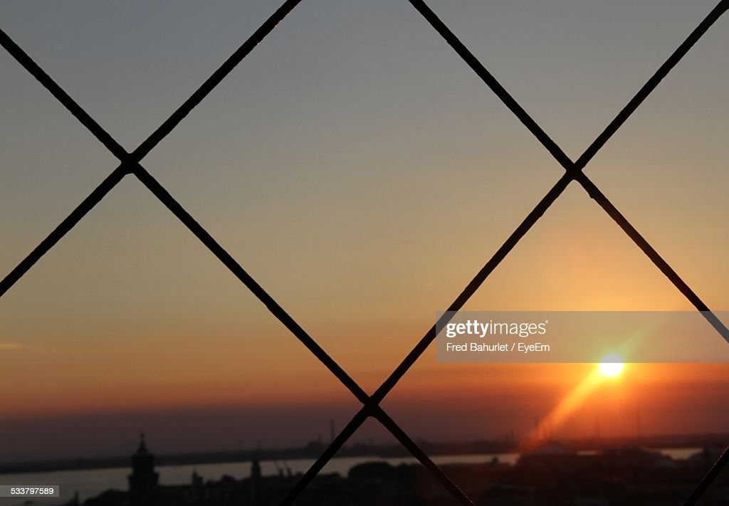 Scenic View Of Sunset Seen Through Metal Fence : Foto stock