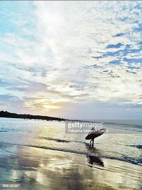 Scenic View Of Surfer On Beach Against Cloudy Sky