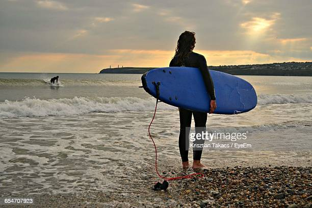 Scenic View Of Surfer Standing On Beach