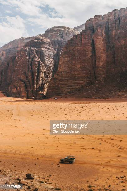 scenic view of suv in wadi rum desert - jordan middle east stock pictures, royalty-free photos & images