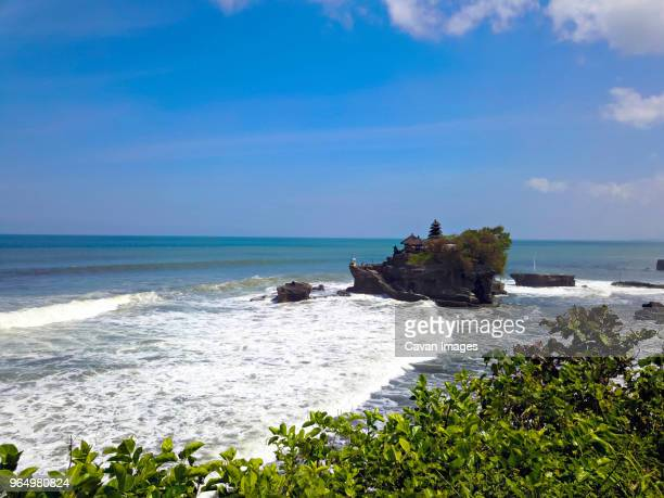 scenic view of tanah lot temple in sea against sky - tanah lot stock pictures, royalty-free photos & images