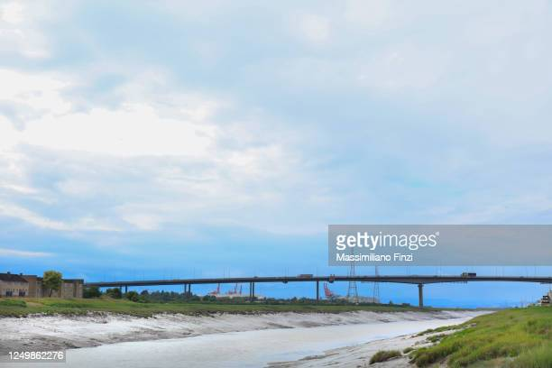 scenic view of the avon river in low tide with the m5 on the avonmouth bridge and blue sky. somerset. uk - avonmouth stock pictures, royalty-free photos & images