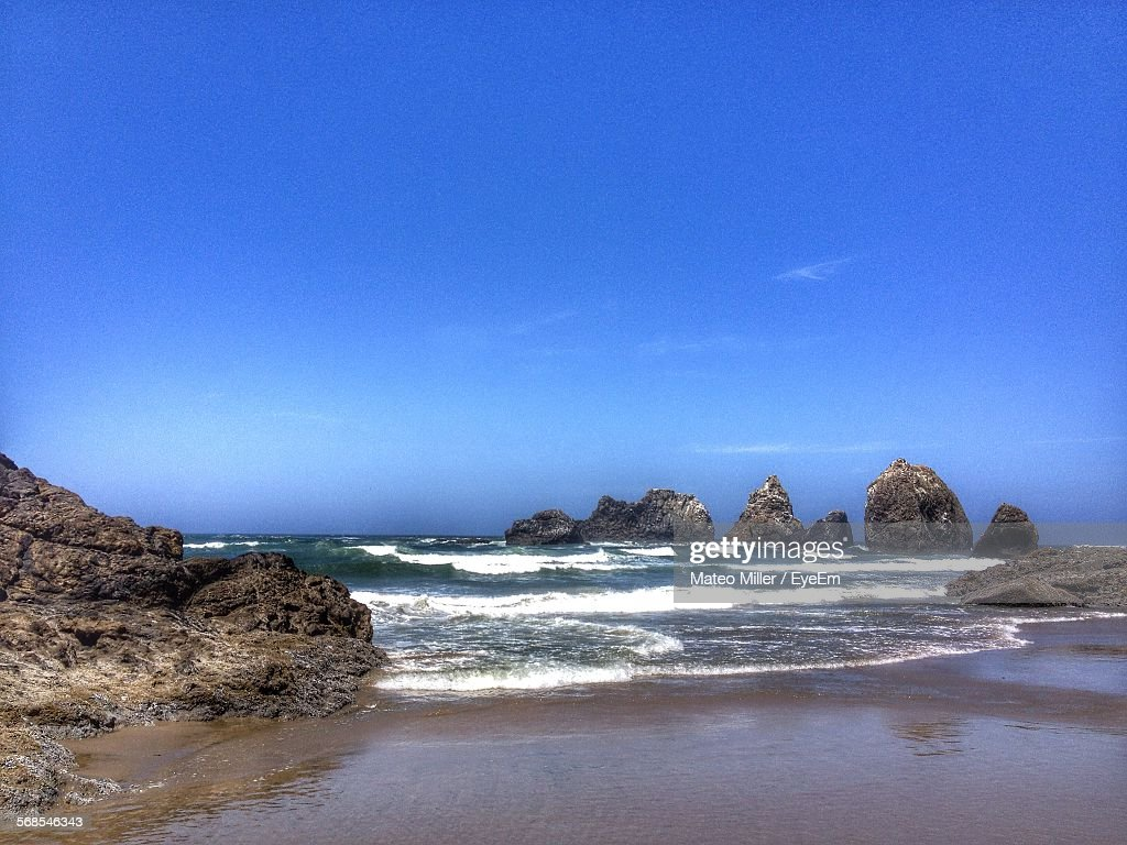Scenic View Of Three Arch Rocks Against Blue Sky : Stock Photo