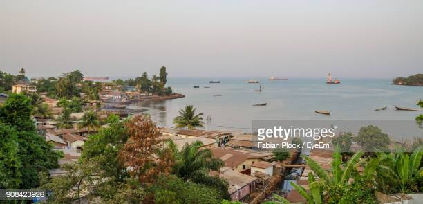 scenic view of town by sea against clear sky - sierra leone stock-fotos und bilder