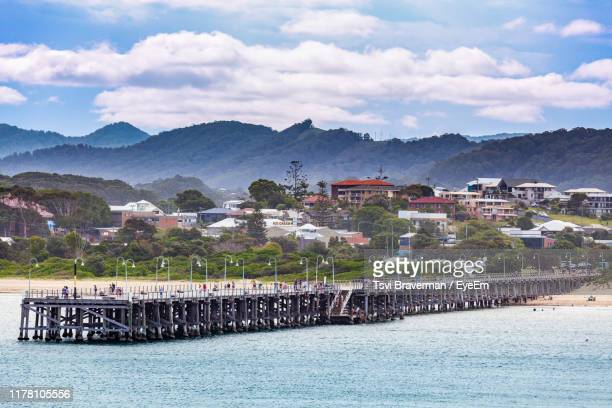 scenic view of town by sea against sky - coffs harbour stock pictures, royalty-free photos & images