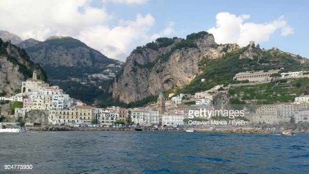 scenic view of town by sea against sky - marica octavian stock photos and pictures