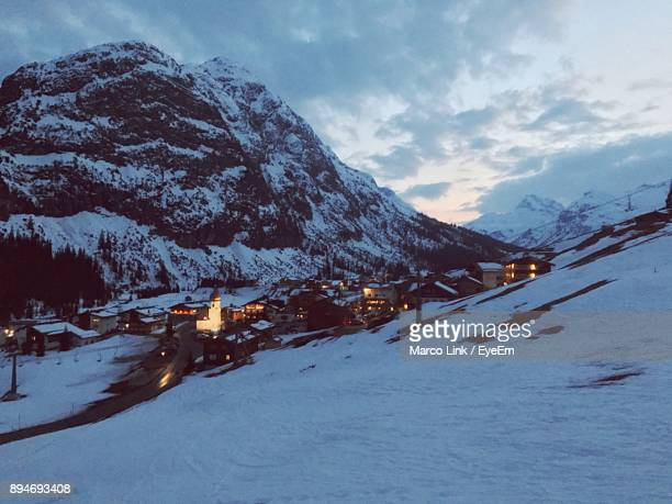 scenic view of town on snowcapped mountains against sky - lech stockfoto's en -beelden