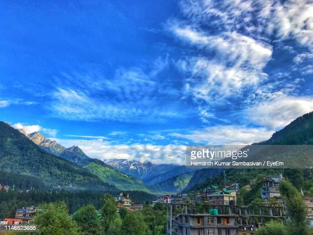 Scenic View Of Townscape And Mountains Against Blue Sky