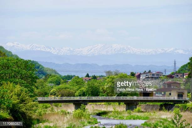 scenic view of townscape by mountains against sky - townscape stock pictures, royalty-free photos & images