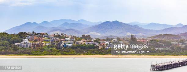 scenic view of townscape by mountains against sky - coffs harbour stock pictures, royalty-free photos & images