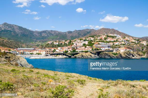 scenic view of townscape by mountains against sky - catalonië stockfoto's en -beelden