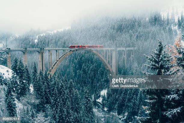 scenic view of train on viaduct in switzerland - european alps stock photos and pictures