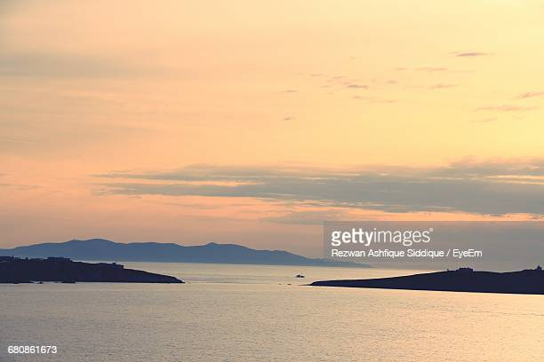 scenic view of tranquil sea at sunset - ver a hora stockfoto's en -beelden